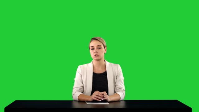 en kvinnlig nyhetsläsare som presenterar nyheter, lägga till din egen text eller bild skärm bakom henne på en grön skärm, chroma key - sitta bildbanksvideor och videomaterial från bakom kulisserna