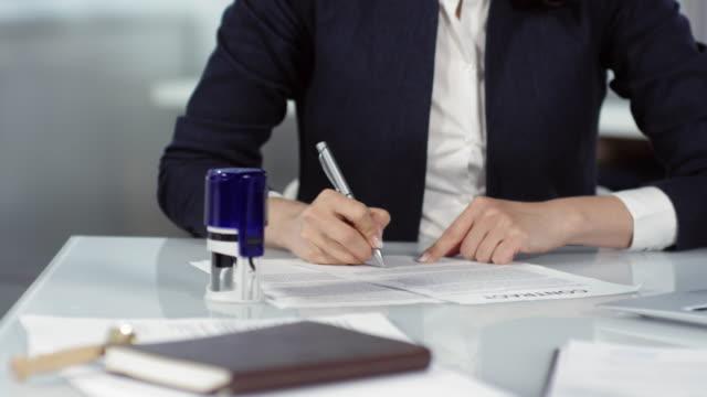 vidéos et rushes de contrat de témoin et d'estampillage de notaire féminin - notaire