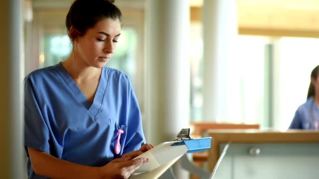 vidéos et rushes de infirmière vérification des notes dans un couloir de l'hôpital - infirmier