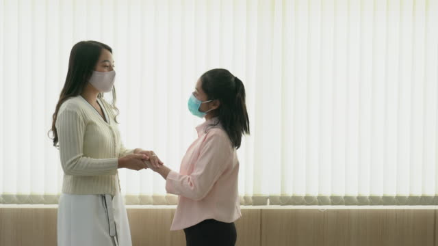 Female nurse comforting patient in a hospital