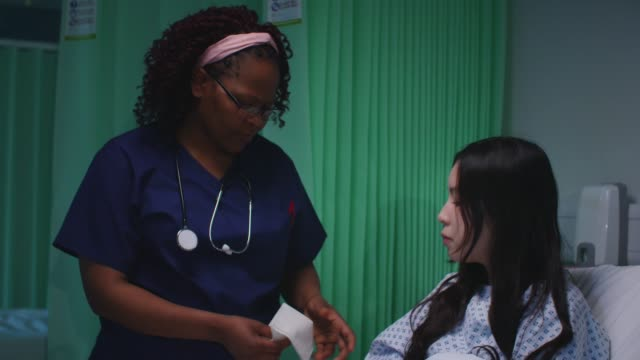Female Nurse Gives Patient a Tissue Side view close up of a mixed race female patient wearing hospital gown, sitting up in a hospital bed, talking with an African American female doctor wearing blue scrubs who gives her a tissue. nhs stock videos & royalty-free footage