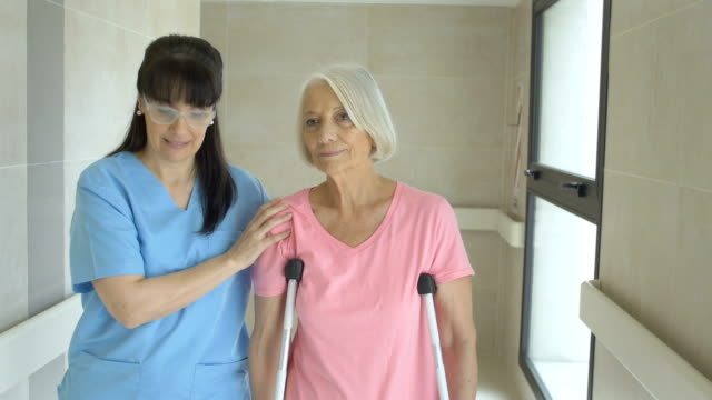 Female nurse helping senior woman on crutches Mature female nurse helping senior woman on crutches. Medical professional is walking with disabled patient. They are on corridor in rehab center. crutch stock videos & royalty-free footage