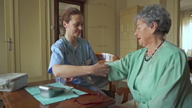 vídeos y material grabado en eventos de stock de mujer enfermera de medir la presión sanguínea de una mujer y comunicarse con ella durante la visita. - servicios sociales