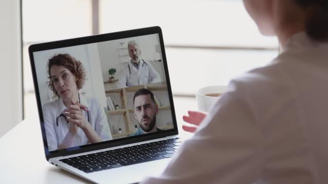stockvideo's en b-roll-footage met vrouwelijke verpleegster die jonge en oude artsenteamvideoconferentie deelneemt - corona scherm