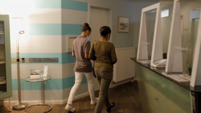 vídeos de stock e filmes b-roll de female nurse receiving a patient - clínica médica