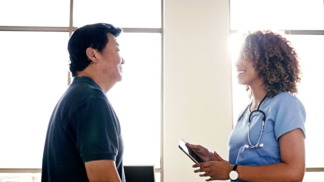 Female nurse talks with senior male patient Attentive senior Asian man talks withe doctor or nurse during a medical exam. The doctor is holding a digital tablet. cardiologist stock videos & royalty-free footage