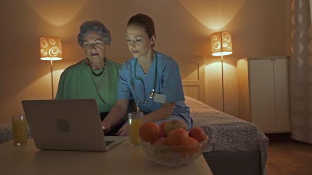vídeos de stock, filmes e b-roll de feminina enfermeira ensinando uma velha usar o laptop em casa. - assistência à terceira idade