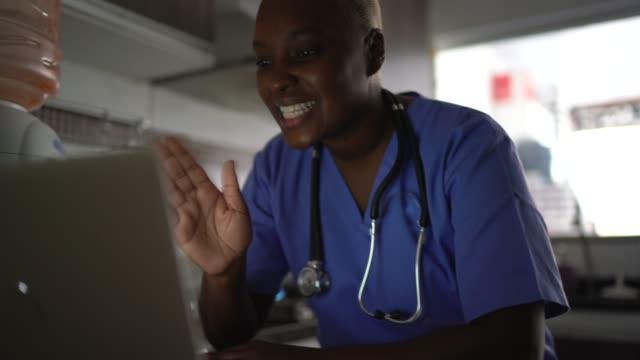 weibliche krankenschwester / arzt macht einen videoanruf mit laptop - abgeschiedenheit stock-videos und b-roll-filmmaterial
