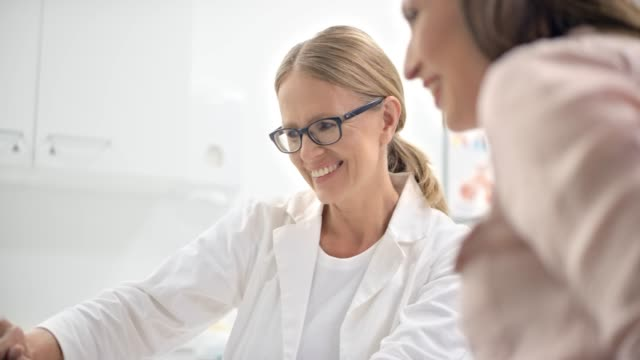 Female OB-GYN smiling while talking to her pregnant patient and showing her the ultrasound photo on the computer