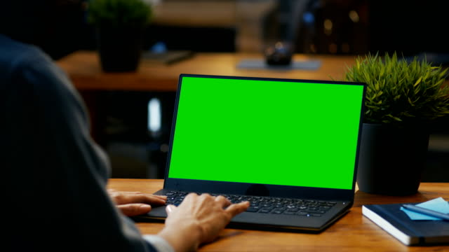 vídeos de stock e filmes b-roll de female office worker at her desk works on a laptop with mock-up green screen. over the shoulder footage. she sits at the wooden desk in creative office. - modelo arte e artesanato