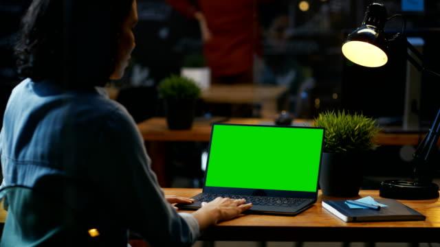 vídeos de stock, filmes e b-roll de trabalhador de escritório feminino em seus trabalhos de secretária em um laptop com mock-up de tela verde. durante as filmagens de ombro. ela se senta na mesa de madeira no escritório criativo. - mockup