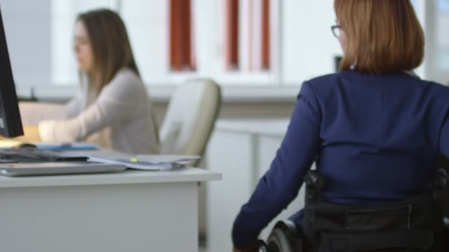 Female Office Worker in Wheelchair Reading Documents at Desk