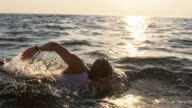 istock SLO MO TS Female open water swimmer swimming forward crawl in the sun 1024363550
