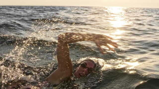slo mo ts nuotatrice donna in acque libere che nuota davanti a strisciare nel mare sotto il sole - braccio umano video stock e b–roll
