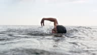 istock Female open water swimmer swimming front crawl in the sea 1024608126