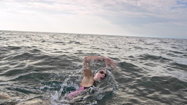 vídeos de stock e filmes b-roll de slo mo female open water swimmer swimming in the choppy waters of the ocean - swim arms