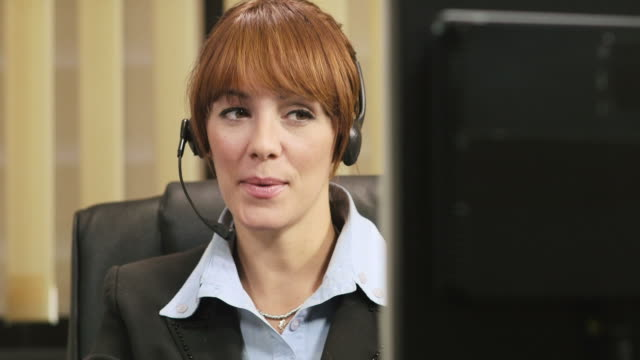 female operator in call center working as customer service representative woman working as customer service representative in call center, talking on telephone with headset hands free device stock videos & royalty-free footage
