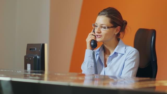 femmina operatore della reception dell'hotel parla al telefono - rispondere video stock e b–roll