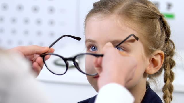 weibliche augenärztin wählt brille für lächelndes kleines mädchen, optischer rahmen - augenheilkunde stock-videos und b-roll-filmmaterial