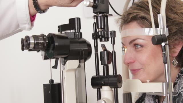 vidéos et rushes de ophtalmologiste femelle examinant les yeux des femmes - examen ophtalmologique