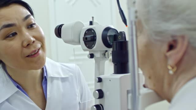 Female Ophthalmologist Using Slit Lamp during Eye Exam