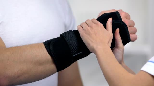 vídeos de stock, filmes e b-roll de sustentação de pulso desgastando ortopédica fêmea ao paciente masculino, tratamento do traumatismo - punho
