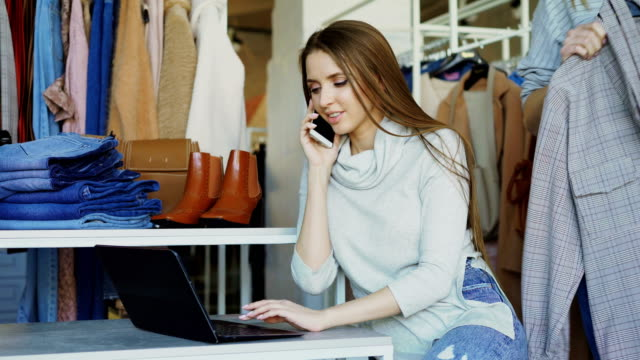 female owner of clothing boutique is talking on mobile phone and typing on laptop. her assistant is approaching her, and she is giving orders in friendly manner - owner laptop smartphone video stock e b–roll