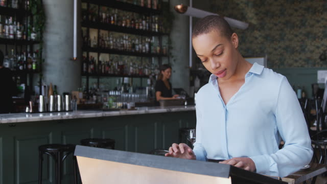 Female Owner Of Restaurant Bar Standing By Counter Checking Reservations Before Service video