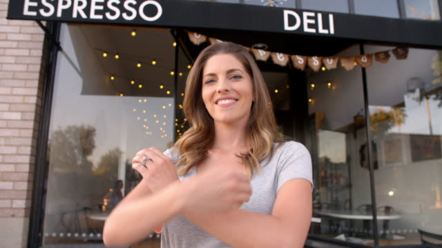 Female owner walks into focal plane outside coffee shop - video