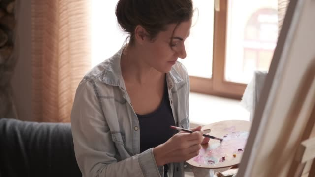 female painter painting a picture on canvas - tavolozza video stock e b–roll