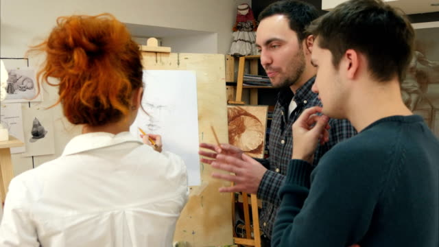 Female painter teaching young men how to draw classical portrait video