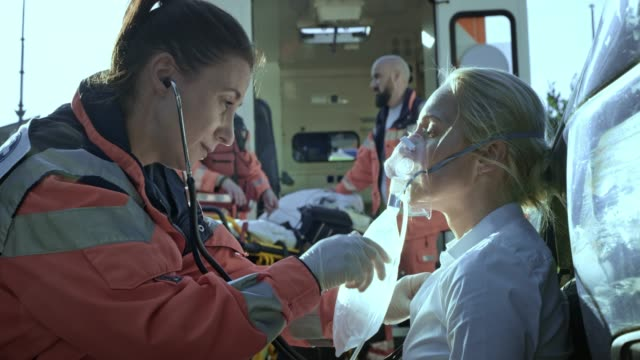 vídeos de stock e filmes b-roll de female paramedic talking to the injured woman sitting on the ground at the scene of a car accident and breathing with the oxygen mask - resgate