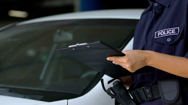 Female parking warden signing ticket and attaching it to car windshield, rules