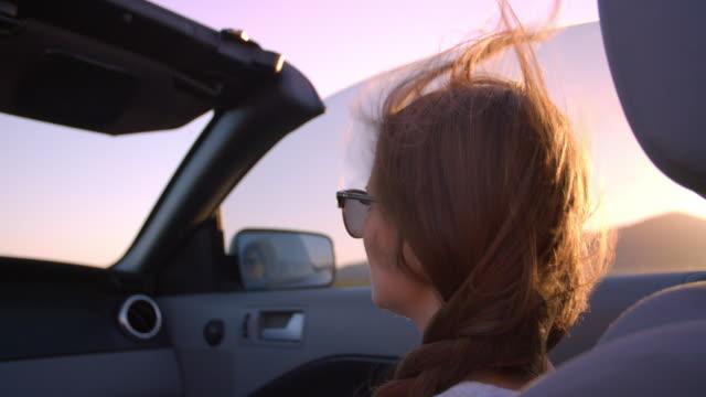 femmina passeggeri guida in auto convertibile scatto su r3d - spettinato video stock e b–roll