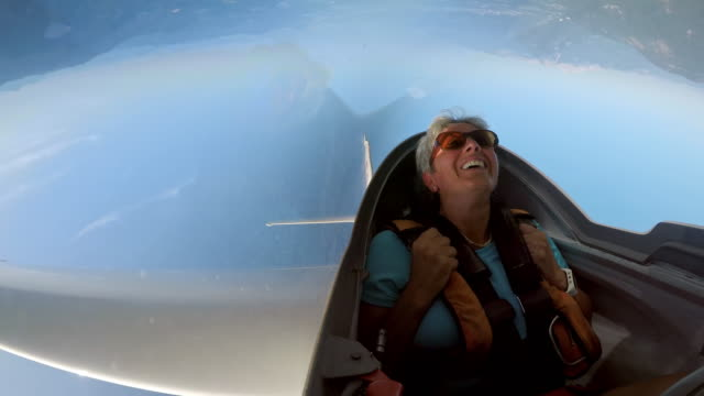ld female passenger laughing while looping in the glider in the sunny sky - sedili aereo video stock e b–roll