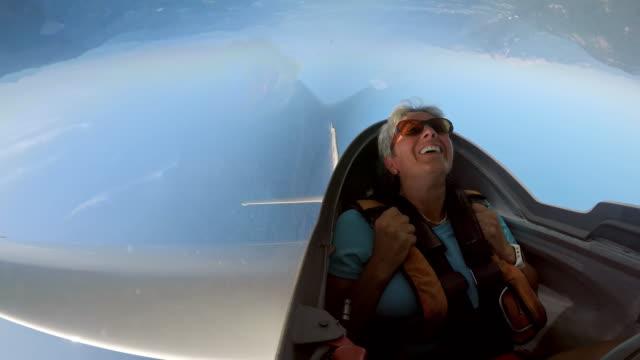 vidéos et rushes de passager de ld femelle rire tout en boucle dans le parapente dans le ciel ensoleillé - vue en contre plongée verticale