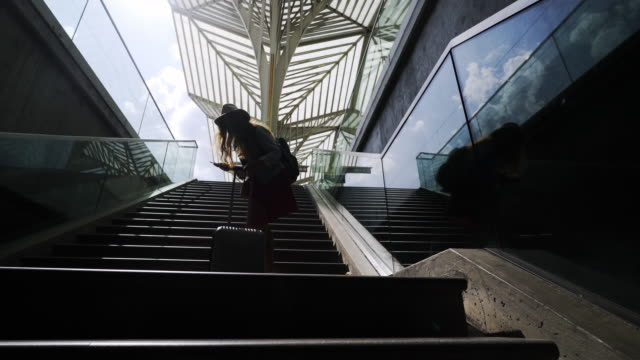 female passenger with suitcase walking up stairs on station - donna valigia solitudine video stock e b–roll