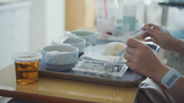 female patient eating hospital food - taca filmów i materiałów b-roll