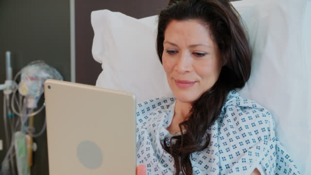 Female Patient In Hospital Bed Using Digital Tablet video