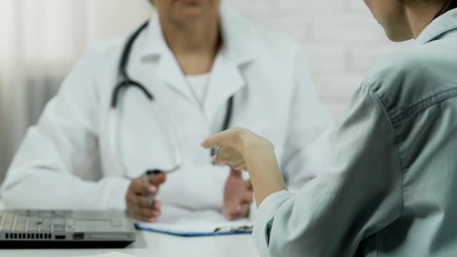 여성 환자 의사 룸, 나쁜 뉴스에서 불 치의 질병에 대 한 듣기 - aids 스톡 비디오 및 b-롤 화면