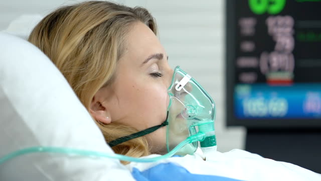 kvinnliga patienten liggande sjukhussäng med syrgasmask, monitor visar vitala tecken - kvinna ventilationssystem bildbanksvideor och videomaterial från bakom kulisserna