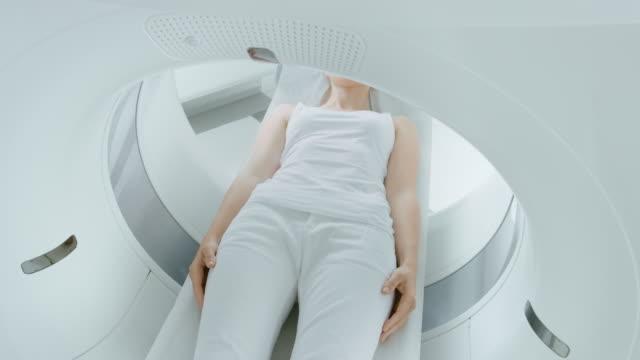 女性患者は、ct または mri スキャンの上に横たわる、ベッドはマシン スキャン彼女の身体と脳の中に動いています。ハイテク機器と医療研究室。高所カメラ ショット。 - 医療用スキャン点の映像素材/bロール