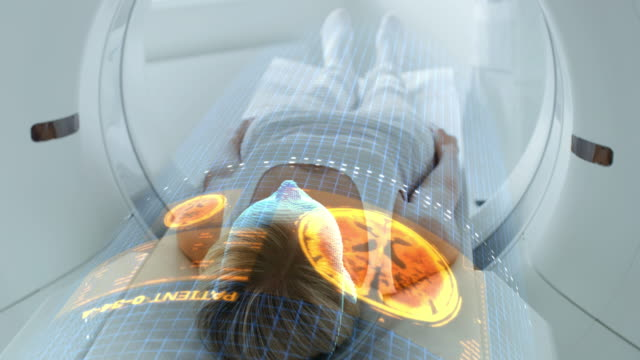 Female Patient Lying on CT or PET or MRI Scan Bed, Moving Inside the Machine While it Scans Her Brain and Vital Parameters. Augmented Reality Concept with VFX In Medical Lab with High-Tech Equipment.
