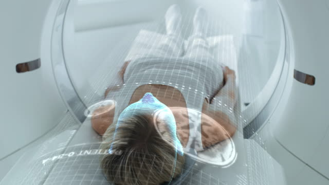 vídeos de stock e filmes b-roll de female patient lying on ct or pet or mri scan bed, moving inside the machine while it scans her brain and vital parameters. augmented reality concept with vfx in medical lab with high-tech equipment. - exame médico procedimento médico