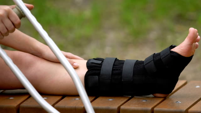 Female patient with crutches massaging painful leg in walking brace, outdoors Female patient with crutches massaging painful leg in walking brace, outdoors crutch stock videos & royalty-free footage