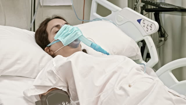 vídeos de stock e filmes b-roll de female patient with infectious disease lying in hospital bed - covid hospital bed respirator
