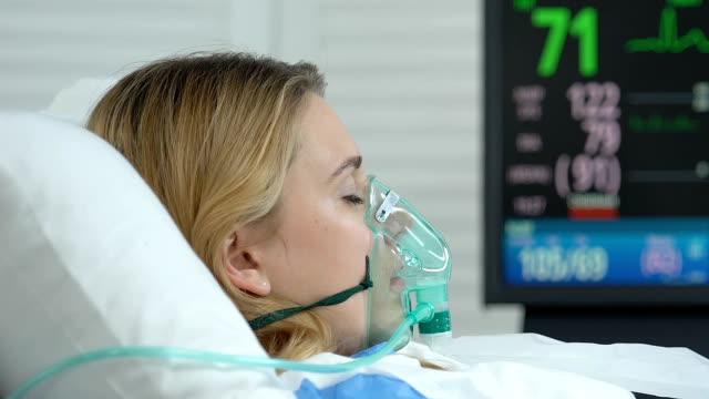 kvinnlig patient med syrgasmask liggande sjukhussäng, akutmedicin operation - kvinna ventilationssystem bildbanksvideor och videomaterial från bakom kulisserna