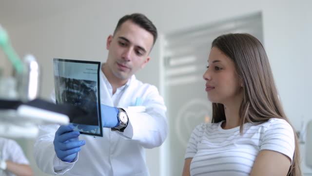 vídeos y material grabado en eventos de stock de la paciente femenina está en la oficina del dentista para una radiografía - ortodoncista