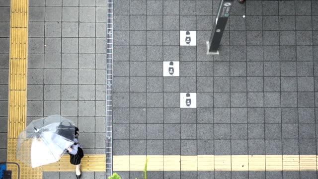 Female pedestrian walking holding umbrellas in slow motion in aerial view video