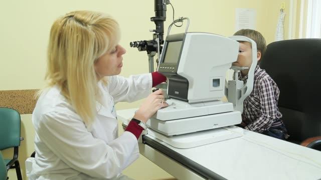 vidéos et rushes de female opticien pédiatrique examine les yeux du petit garçon avec dispositif de lampe à fente. - réfracteur